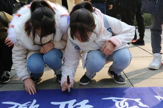 徒步参与者在活动横条上签名。