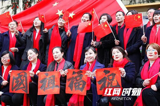 教师手举红旗,祝福祖国。