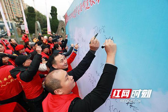 大家纷纷在签名墙上签下自己的名字。