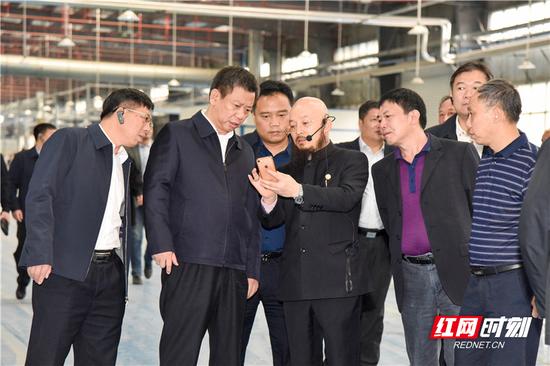 东莞桂阳商会会长周劲松向领导介绍楚荣家居生产情况。