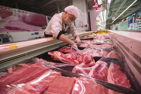 山西省太原市一家超市的工作人员在给猪肉套保鲜膜。