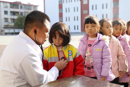 医生正在为学生进行先心病筛查。