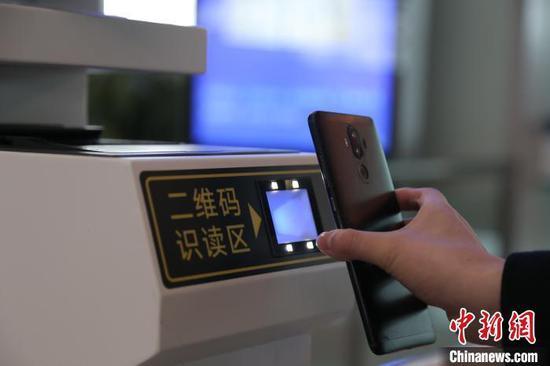 图为旅客使用客票二维码检票乘车。翟灏 摄