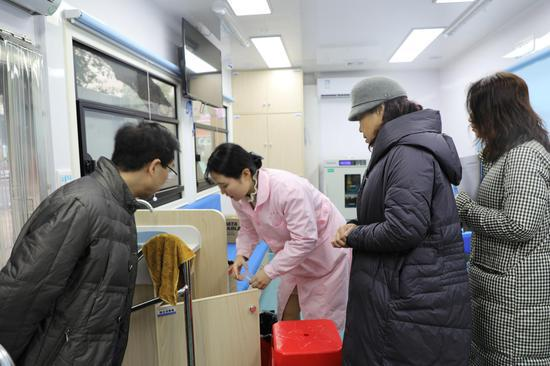 血站站长李孟祥(左一)带队检查献血车内设施设备