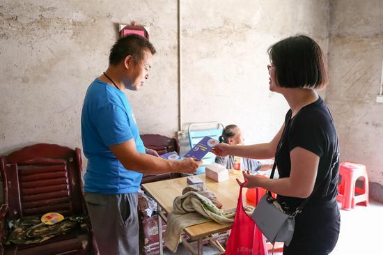 市扶贫办党员志愿者向她儿子发放政策资料。