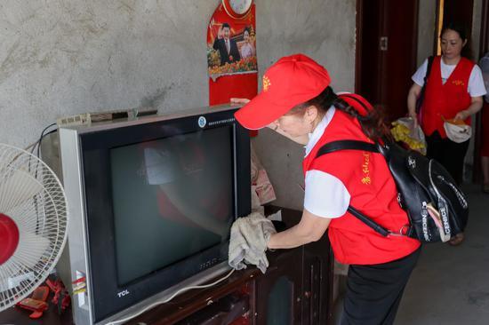 志愿者帮助贫困户刘玉莲搞卫生。