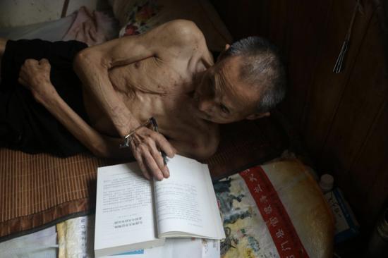 陈集贤老人躺在床上看书