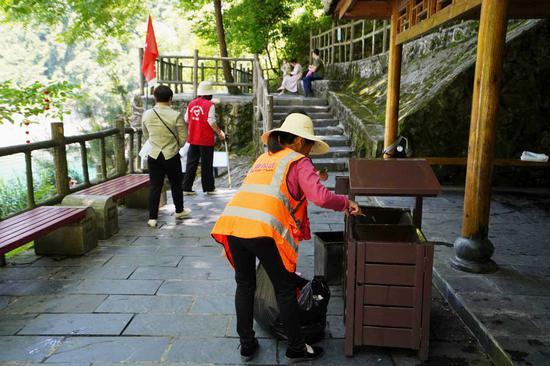 志愿者与景区保洁人员共同维持景区卫生