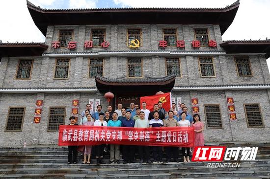 """临武县教育局机关党支部成员在""""六位支书一台戏""""专题展览馆前合影纪念"""