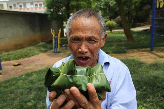 一个老人拿着自已包的粽子乐了。