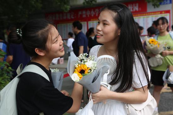考生们接到家长鲜花后,与考生们在一起交流考试体会,露出了满意的笑容。