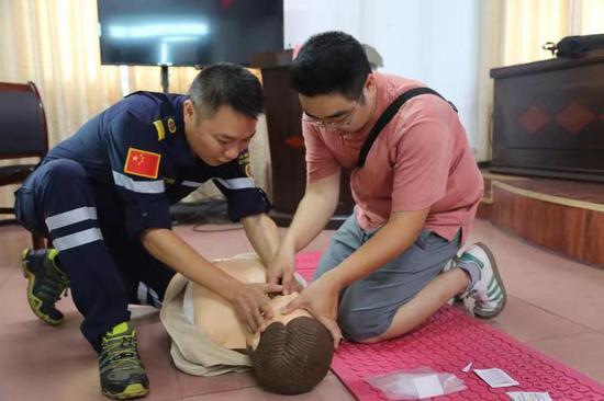 应急救援队队员正教参加培训人员怎样清除口中异物,进行胸外挤压和人工呼吸。