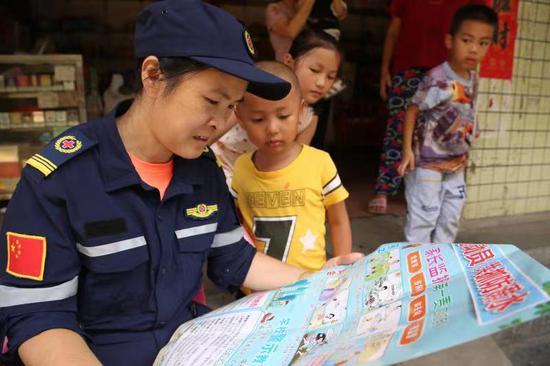 """资兴市志愿者协会""""红十字""""应急救援队上门,向小朋友宣传《全体总动员 共抓防溺水》有关宣传资料"""