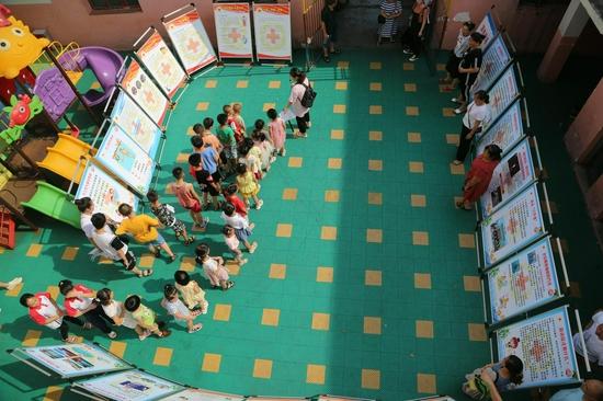 """兴市志愿者协会""""红十字""""应急救援队队队员组织小朋友观看防溺水知识展览。"""