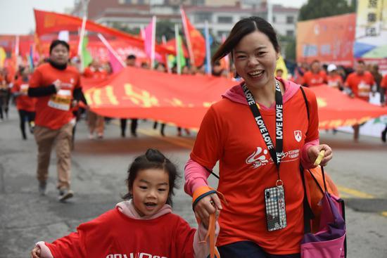 """赛道上,一对母女体验迷你马拉松""""欢乐跑""""。"""