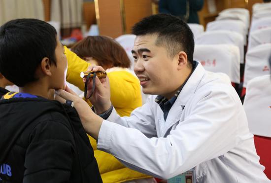 外科专家为三年级以下的学生们进行外科体检筛查。