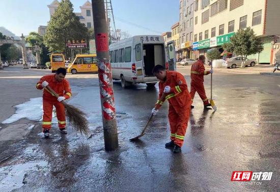 嘉禾县应急救援中队紧急出动在结冰路面撒工业盐融冰,用铁锨铲冰作业。