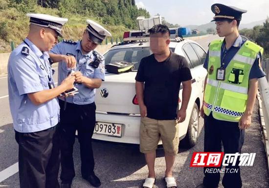 新邵大队民警正在对醉酒男子进行酒精测试。