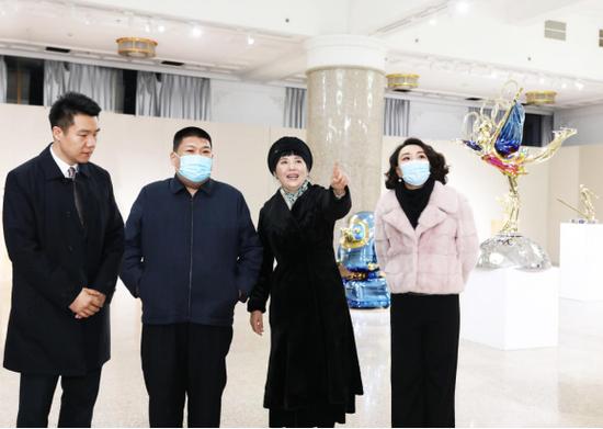雕塑家黄剑向毛新宇将军和夫人刘滨介绍奥运雕塑作品