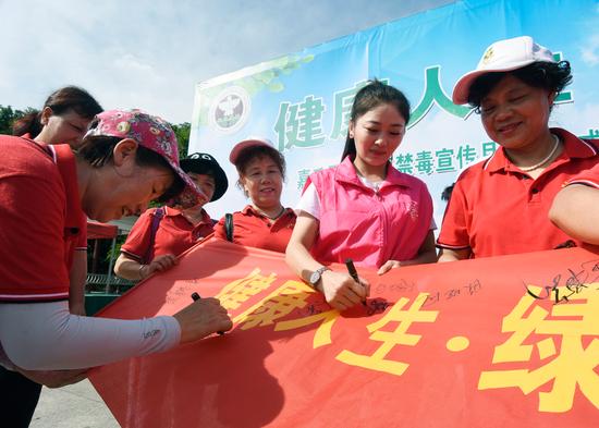 6月23日,嘉禾县珠泉镇丙穴社区,禁毒志愿者在横幅上签名。