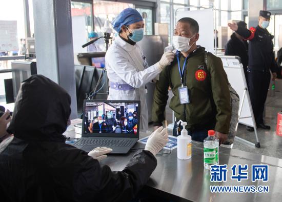 2月24日,在娄底南站进站口,工作人员为返岗复工人员测量体温。