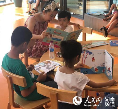 长沙市图书馆内家长带着孩子看书识图。
