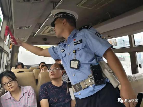 怀化交警上车检查客车灭火器等安全设施。