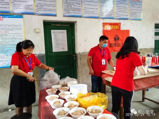 图:志愿者一起给小朋友们分配食材