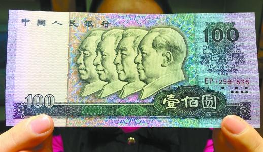 3月22日,中国金币总公司工作人员在长沙展示第四套人民币100元面值的纸币。 湖南日报记者徐行摄