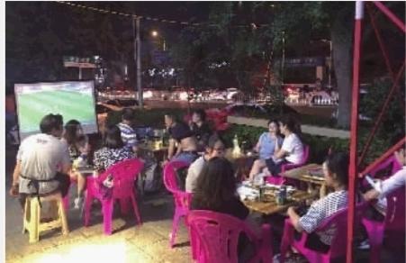 6月13日深夜,市民们在长沙市人民西路一家夜宵店外边吃烧烤边看球。