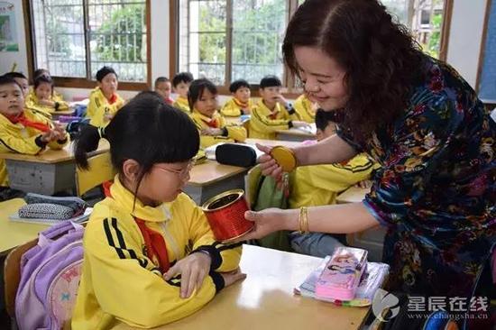 刘利元在给孩子们上作文课,拿着茶叶盒让孩子们细细观察。