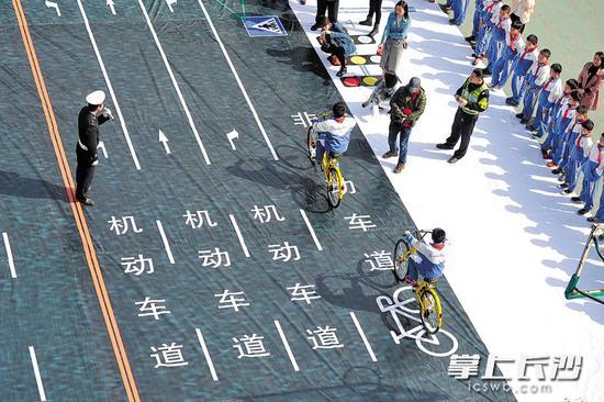"""昨日上午,""""安全骑行""""主题宣传进校园活动在湘雅路三角塘小学举行,通过在学校操场模拟交通十字路口,让小学生学习体验安全骑行方式。 长沙晚报记者 王志伟 摄"""