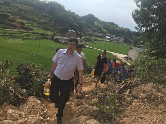 陈志强亲自带领志愿者徒步进村送物资