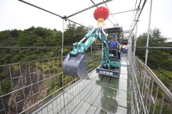 挖掘机碾压湖南平江玻璃桥测承重