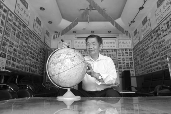 10月8日,暮云新村新正街,83岁的易久藩用笔在地球仪上标记着环球旅行已经到过的国家。图/记者金林