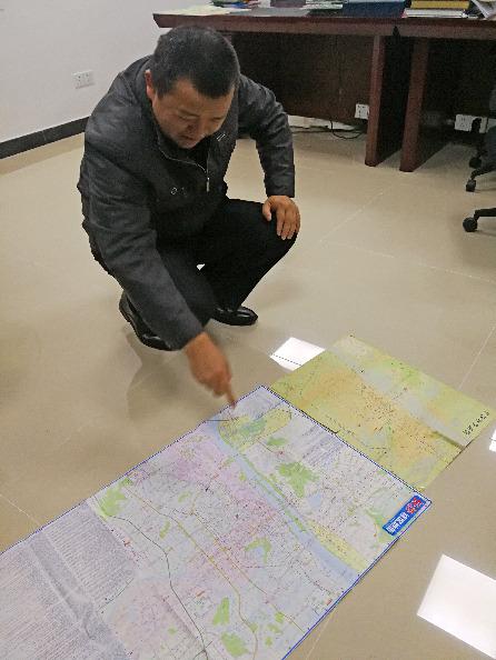 10月23日,蒋连军通过对他收藏的不同时期地图对比,分析改革开放40年长沙城的发展变迁。新华社记者段羡菊摄