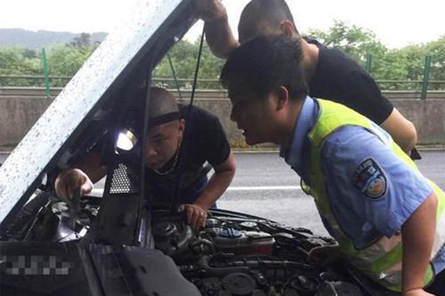 湘潭一汽车在高速上抛锚 交警暴雨中紧急施救