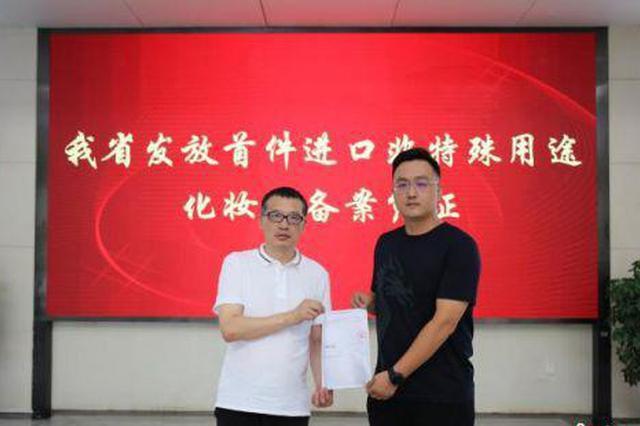 6月2日,湖南省药监局党组书记梁毅恒(左)在长沙向企业颁发了湖南省首件进口非特殊用途化妆品备案凭证。湖南省药监局供图