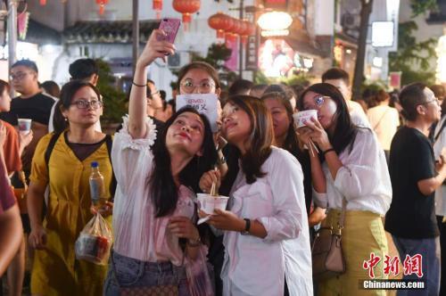 市民在湖南省长沙市街头手持当地美食合影。中新社记者 杨华峰 摄