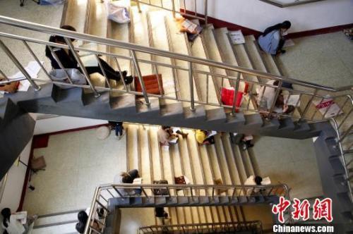图为考研生坐在楼梯上专心背诵。孙宏瑗 摄