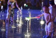 高温解暑新招:市民露天喷泉戏水