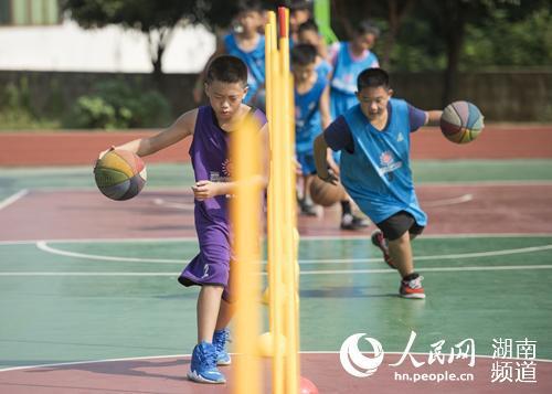 假期篮球场上孩子们正在进行篮球训练。