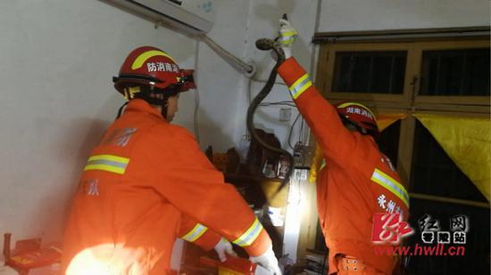 消防队员做好防护措施后,就地利用晒衣杆压住蛇的七寸,并徒手抓住顺势将它放进纤维袋中。