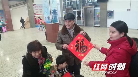 """火车站工作人员为旅客送""""福""""字。"""