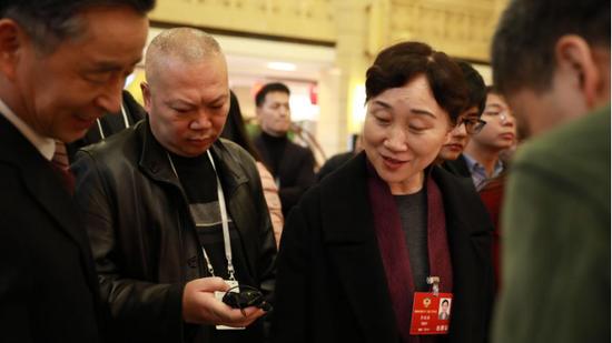 湖南省政协主席李微微(右一)仔细观看各媒体报道内容,新浪湖南工作人员采录聆听她关于对网络新媒体在两会报道中的意见与建议。