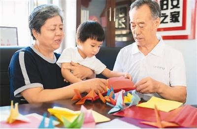 活动现场,老年夫妇代表一起折千纸鹤 丁根厚摄(人民视觉)