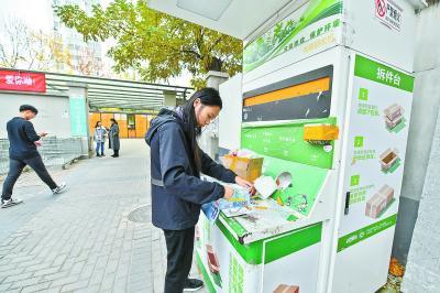 北京林业大学校园内,一名学生收取快递后将包装箱折叠好,准备投入纸箱回收机。北京日报记者 邓伟摄