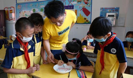 """老师指导同学在自带光盘上绘画""""节约粮食""""图案"""