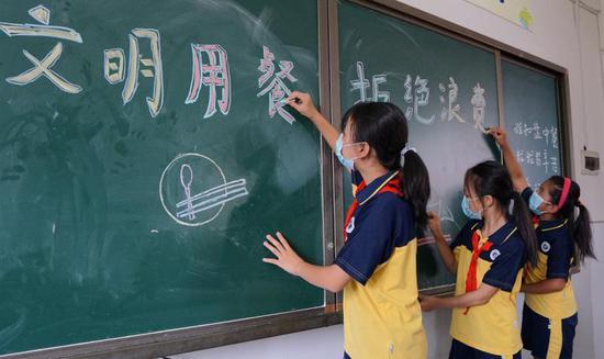 """同学们在黑板上写上新学期班会主题""""文明用餐,拒绝浪费"""""""