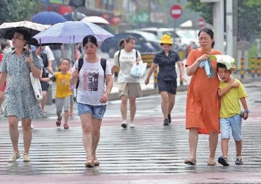 7月18日10时许,长沙市开福区湘江北路,市民在雨中出行。当天,长沙市区出现雷雨天气,局部地区下起大雨,给持续晴热高温的星城带来了一丝凉意。